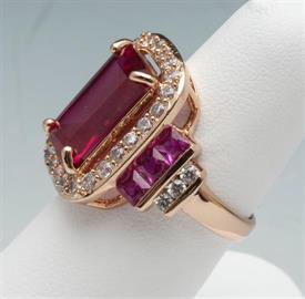 -SIZE 7 1/4 RUBY COLORED CRYSTAL RING WITH GOLD TONE METAL