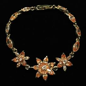 "-,TOPAZ CZ FLOWER BRACELET IN GOLD TONE METAL. 7.25"" LONG."